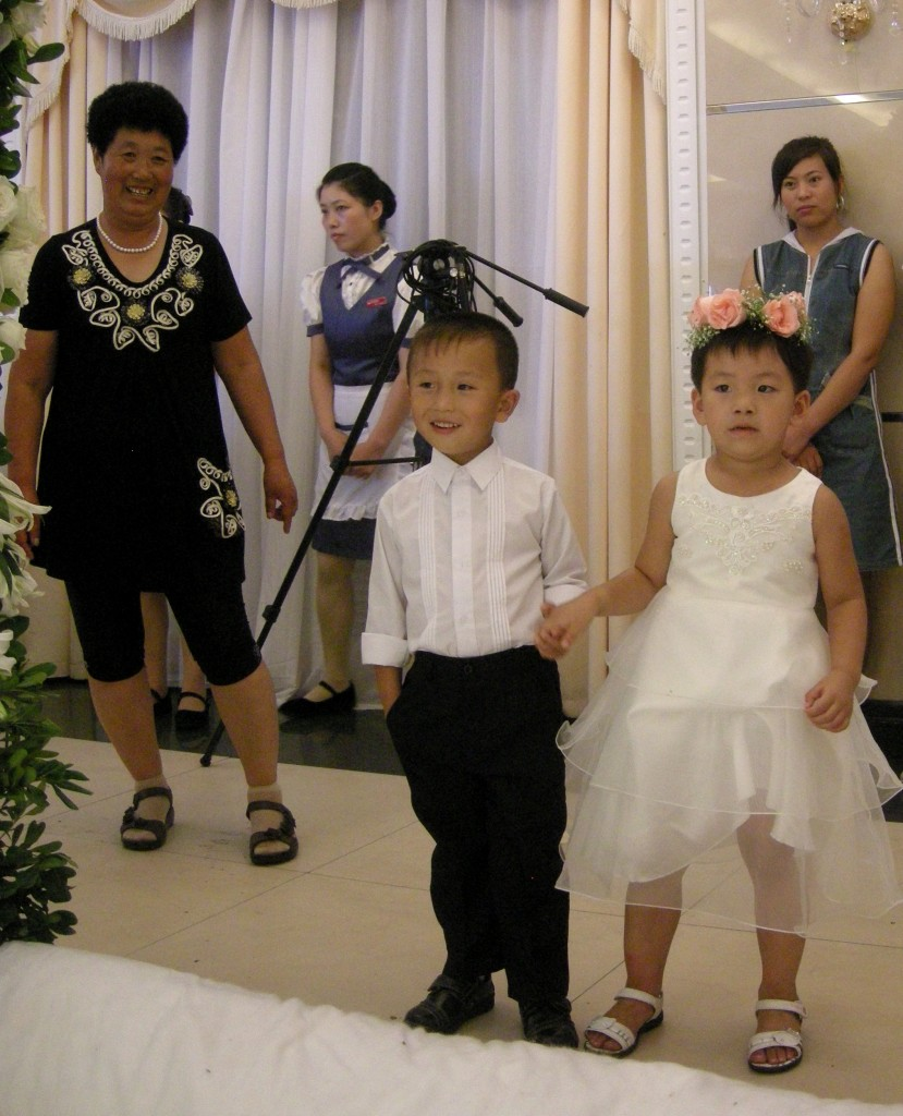The little ones look on under the watchful eye of Jiao Jiao's aunt
