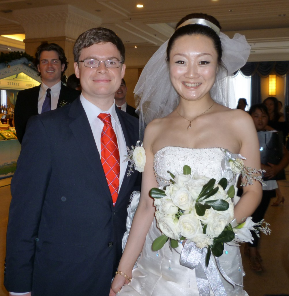 The bride and groom wait in the hotel lobby with Tom looking on